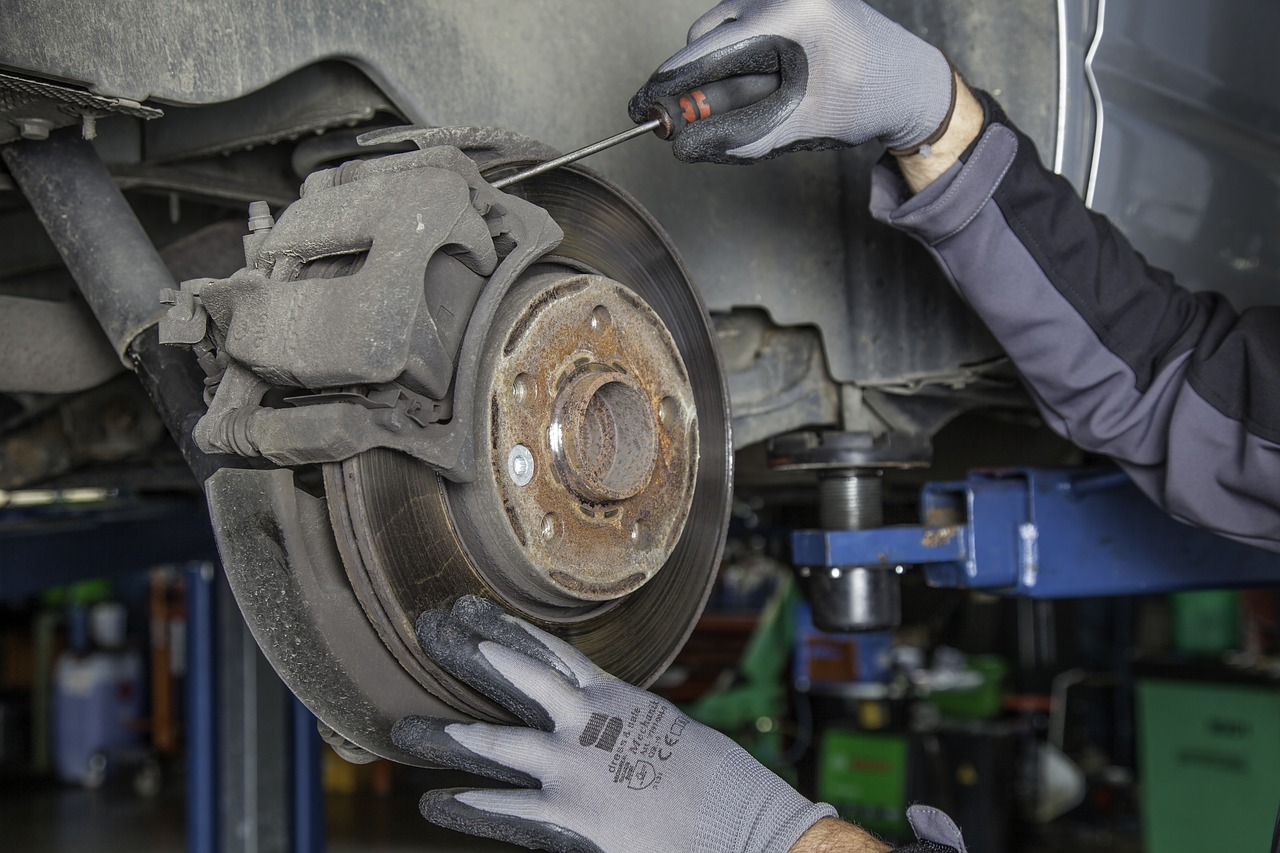 auto mechanic working on a car's breaking system