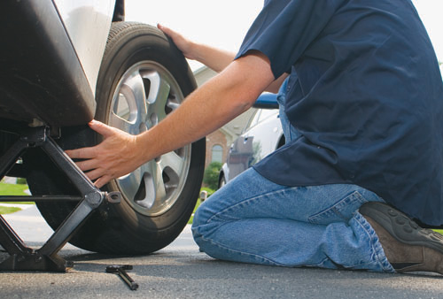 man removing a tire from vehicle