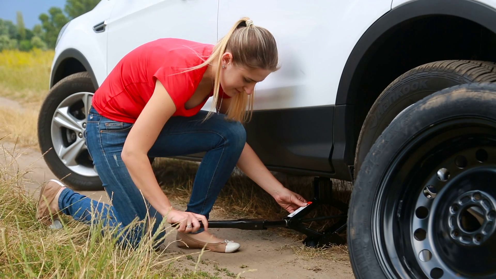 woman changing flat tire